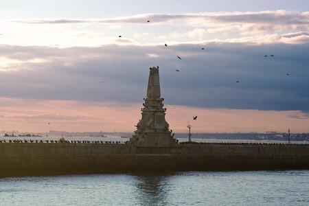 Vieux phare avec des oiseaux sur un jour nuageux