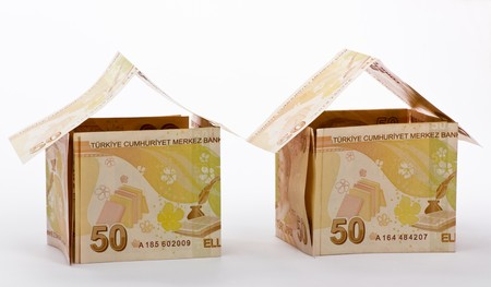 Houses made of banknotes on white background Stock Photo
