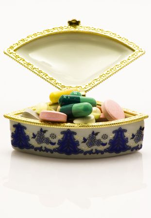 Pills in the litte case over white