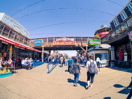 San Francisco, CA, USA - April 3, 2017: Tourists walking near the entrance of Pier 39, Fishermans Wharf, bridge with Bubba Gump Shrimp Co. sign above Editorial