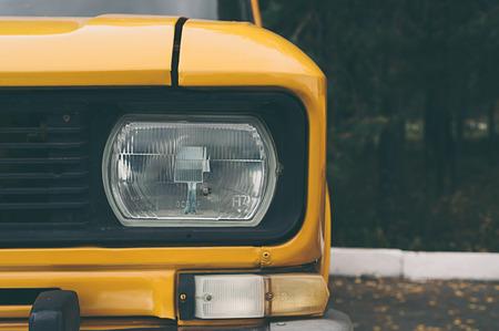 headlights: Close-up of a yellow car headlights