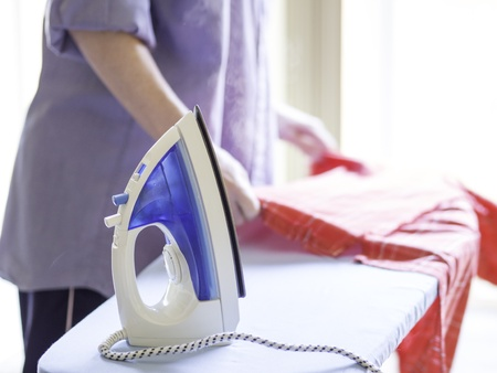 domesticity: Woman ironing a red shirt with a steam iron taken against a bright, airy background