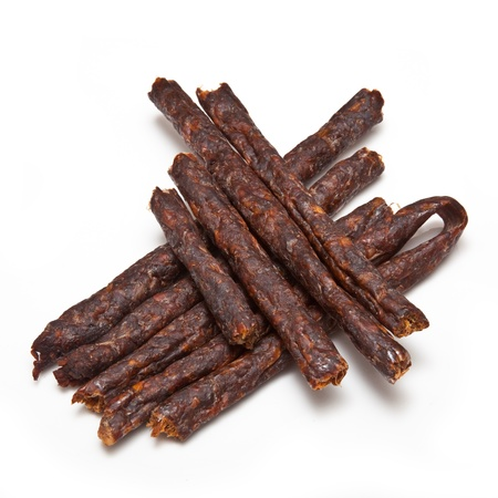 South African spicy Peri peri drywors (dried sausage jerky) isolated on a white studio background.