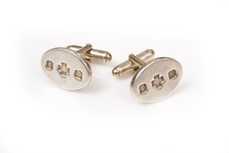 cuff link: Solid silver cuff links isolated on a white studio background.