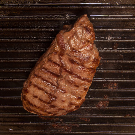 horse meat: Horse meat steak cooking on a griddle,