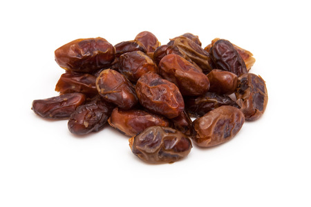 "arabian food: Dried Medjool dates isolated on a white background. Medjool dates are also called ""king of dates,"" the ""diamond of dates,"" or the ""crown jewel of dates"""