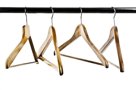 coathangers: Close up of coathangers on clothes rail against white background LANG_EVOIMAGES