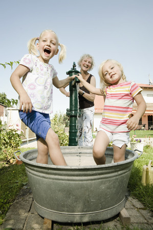location shot: Germany,Bavaria,Grandmother with children playing in water tub LANG_EVOIMAGES