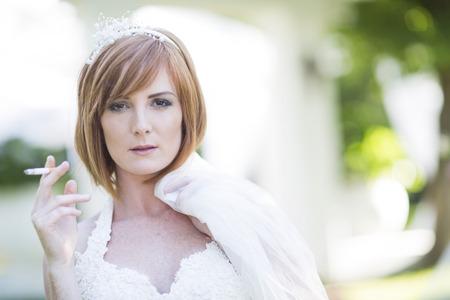location shot: Bride smoking a cigarette before wedding LANG_EVOIMAGES