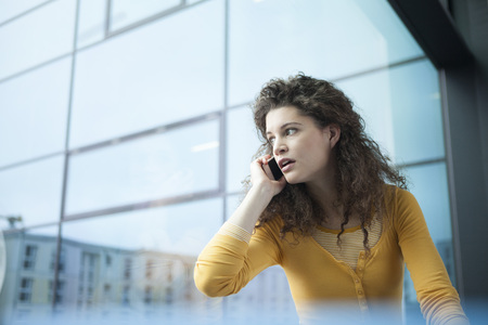 freaked: Frightened young woman on the phone at the window