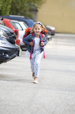 location shot: Little girl on her school way crossing parking area