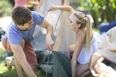 location shot: Happy young couple setting up a tent