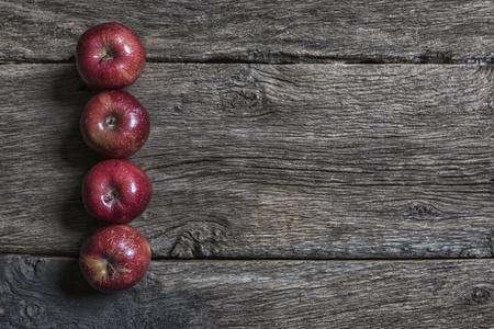 conformance: Four red apples on dark wood LANG_EVOIMAGES