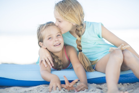 africa kiss: Two happy girls on beach on a lilo
