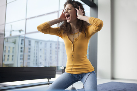Screaming young woman wearing headphones at the window LANG_EVOIMAGES