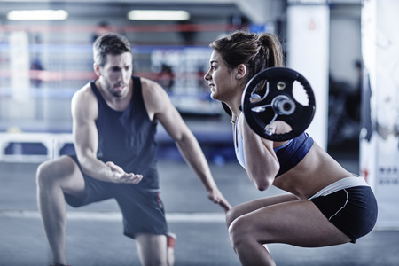 motivations: Trainer watching woman doing fitness training with weights