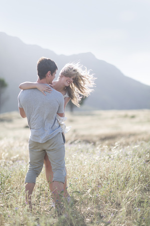 location shot: South Africa, Young couple embracing in field LANG_EVOIMAGES