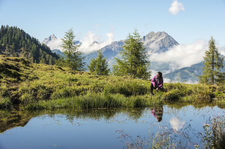 mountaintops: Austria, Altenmarkt-Zauchensee, young woman hiking in alpine landscape LANG_EVOIMAGES