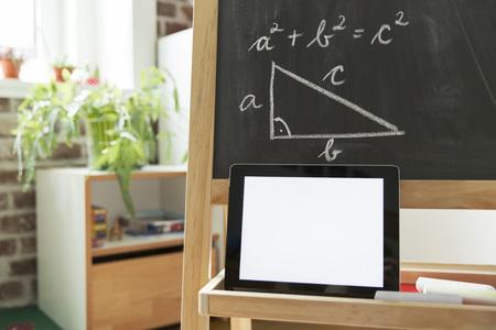 formulae: Tablet computer leaning at blackboard in childrens room