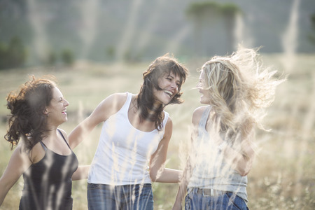 location shot: South Africa, Girl friends dancing and jumping in field