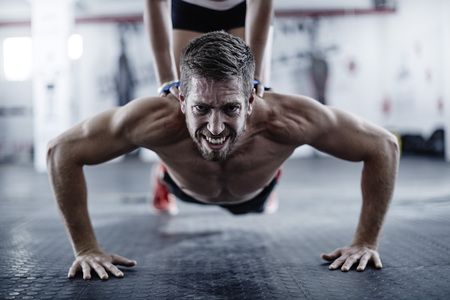 motivations: Man doing push-ups with woman kneeling on his back