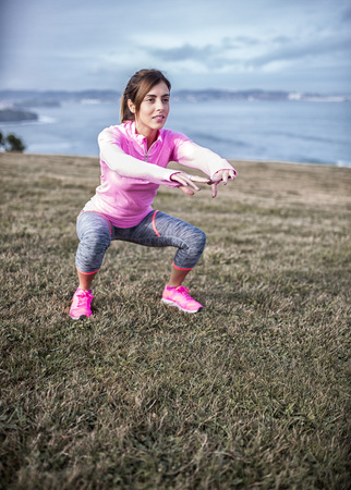 motivations: Spain, Gijon, sportive young woman exercising at the coast