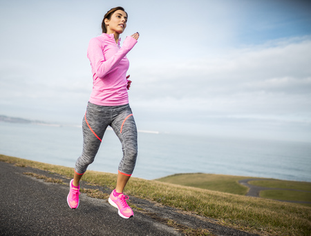 motivations: Spain, Gijon, sportive young woman running on path at the coast