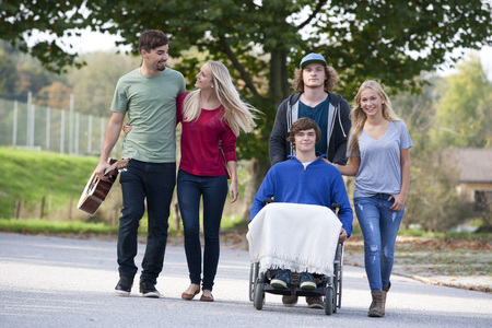 location shot: Young man in wheelchair with friends