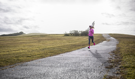 motivations: Spain, Gijon, sportive young woman running on path