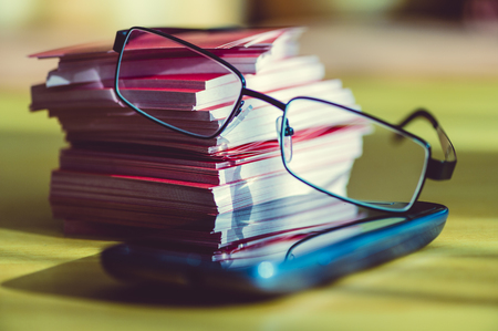 interiour shots: Stacked smart phone, notepads and reading glasses
