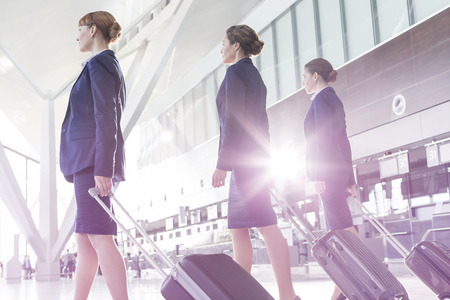 conformance: Three stewardesses with baggage walking at the airport