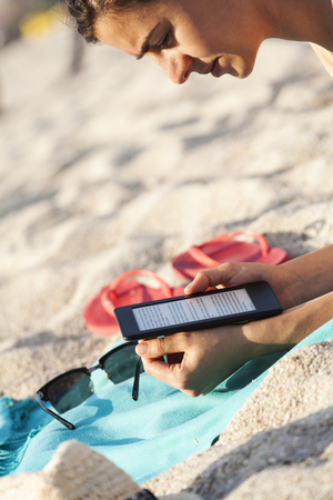sandalias: Grecia, mujer joven leyendo e-book en la playa
