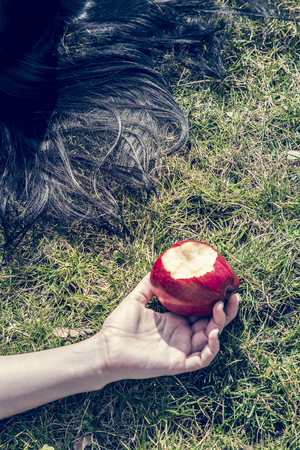 end of a long day: Hand of woman lying on grass holding bitten red apple