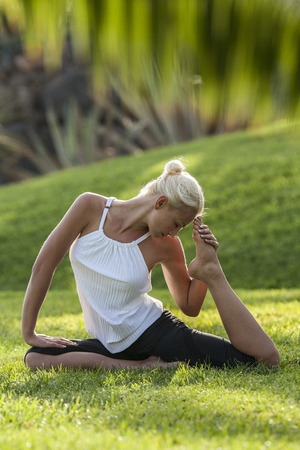 interiour shots: Woman practicing yoga on meadow