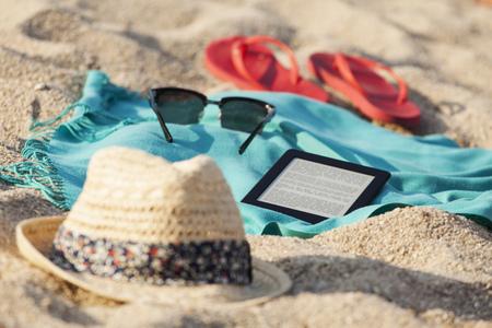 sandalias: Toalla, gafas de sol, flip-flop, sombrero de paja y tableta digital en la playa de arena LANG_EVOIMAGES