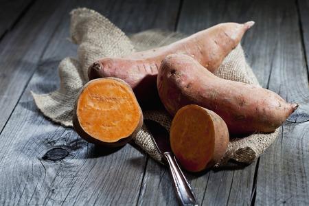 interiour shots: Row sweet potatoand knife on jute, wood