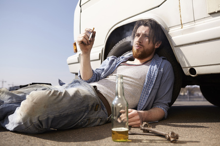 Man leaning against car smoking a cigarette