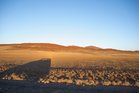 vlei: Africa, Namibia, Sossusvlei, Shadow of a car and sand dunes LANG_EVOIMAGES