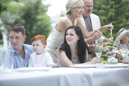 well laid: Woman dishing up salad on a garden party LANG_EVOIMAGES