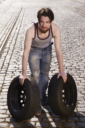 cruddy: Man rolling car tyres LANG_EVOIMAGES