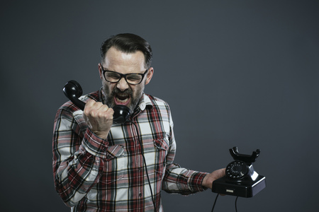 Man screaming into retro telephone in front of grey background