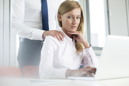 harassing: Colleague harassing businesswoman LANG_EVOIMAGES