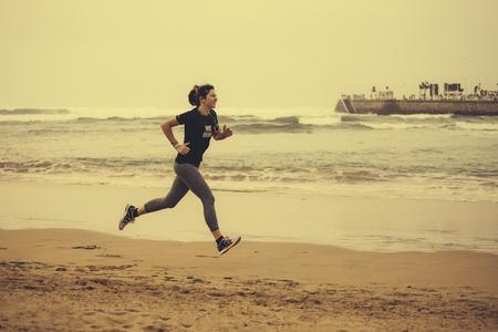 motivations: Spain, Gijon, Woman jogging at the beach