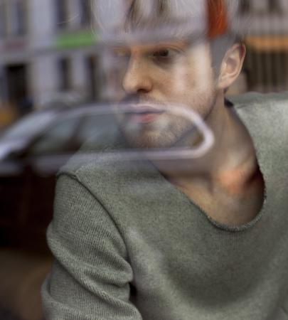 Young man looking through windowpane