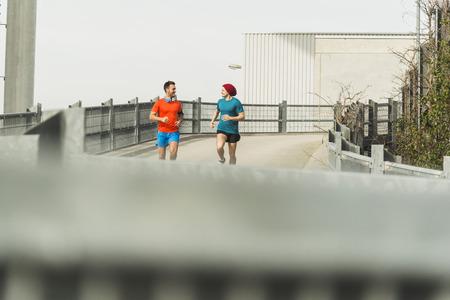 motivations: Two young men jogging on bridge