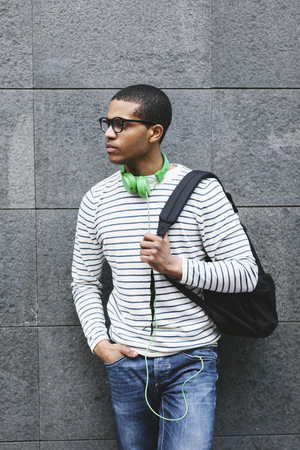 Young man with green headphones and backpack leaning at house front