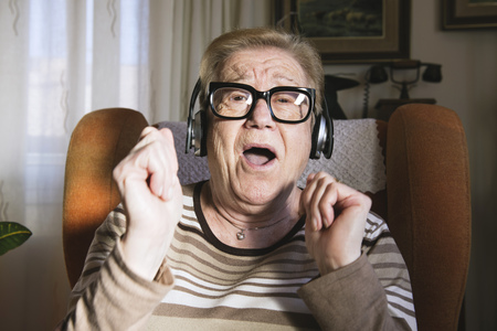 Portrait of happy elderly lady hearing music with headphones LANG_EVOIMAGES