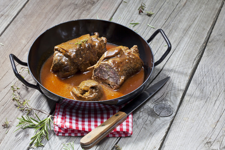 interiour shots: Beef roulades in braising pan, rosmary, kitchen towel and knife on wood