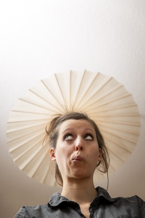 lamp shade: Woman under ceiling lamp as hat