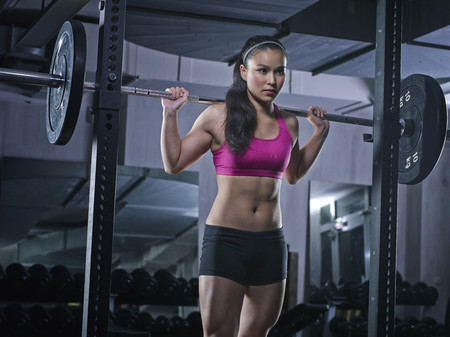 motivations: Young woman doing weightlifting with barbell